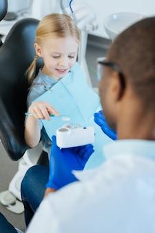 Übung macht den meister. schönes kleines mädchen, das eine zahnbürste benutzt und korrektes zähneputzen übt, während es von ihrem männlichen zahnarzt geführt wird