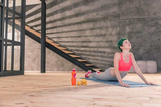 Übungen auf der matte. schlanke junge frau mit rosa top macht morgens übungen auf der sportmatte