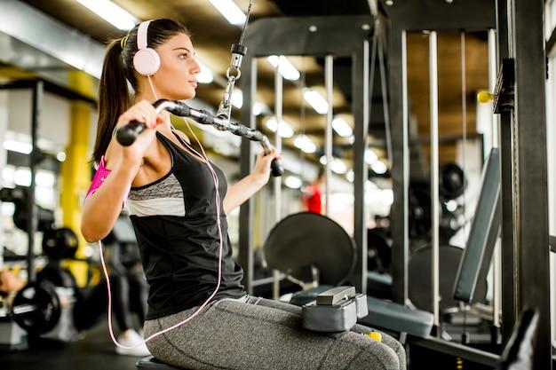 Übungen der jungen frau auf einer übungsmaschine an der turnhalle hörend musik