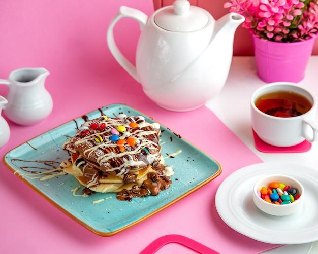 Üppige pfannkuchen mit schokolade und bunten bonbons