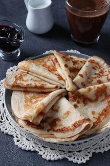 Üppige pfannkuchen mit weizenmehl, eiern und joghurt, serviert mit beerenmarmelade, milch und tasse kaffee auf grauem hintergrund. vertikales format