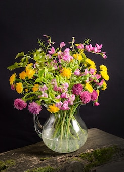 Üppiger strauß wilder blumen in einer vase auf einem schwarzen raum im dunklen stil, blumenstillleben