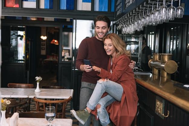 Üppiges fröhliches paar, das telefon benutzt und lacht
