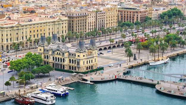 Uferstraße mit vielen menschen, alten gebäuden, grün und festgemachten yachten in barcelona, spanien