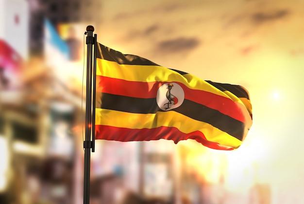 Uganda-flagge gegen stadt verschwommen hintergrund bei sonnenaufgang hintergrundbeleuchtung