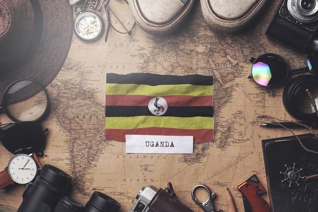 Uganda-flagge zwischen dem zubehör des reisenden auf alter weinlese-karte. obenliegender schuss