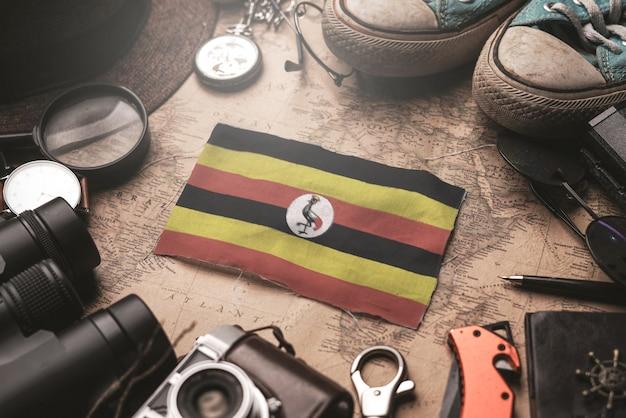 Uganda-flagge zwischen dem zubehör des reisenden auf alter weinlese-karte. touristisches bestimmungsort-konzept.