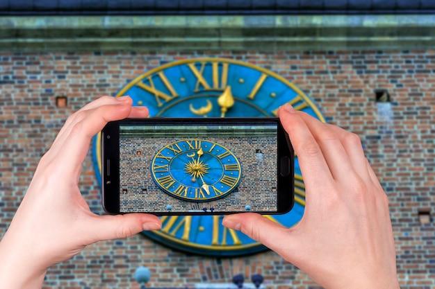 Uhr auf dem rathaus-turm am hauptplatz in krakau nahaufnahme, polen. tourist macht ein foto