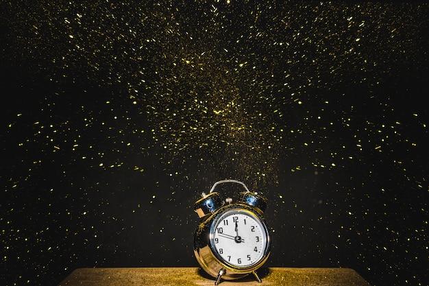 Uhr auf dem tisch mit fallenden pailletten