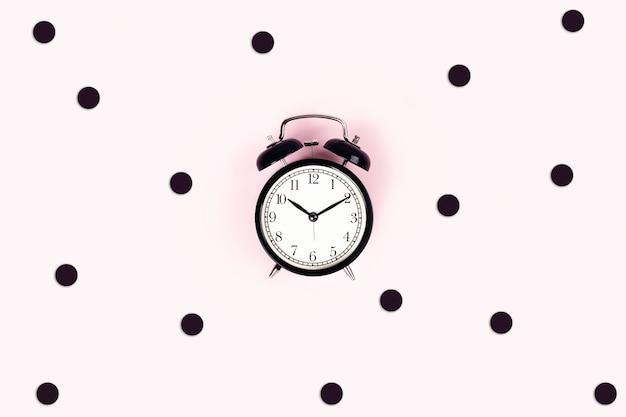 Uhr auf einem rosa tisch.