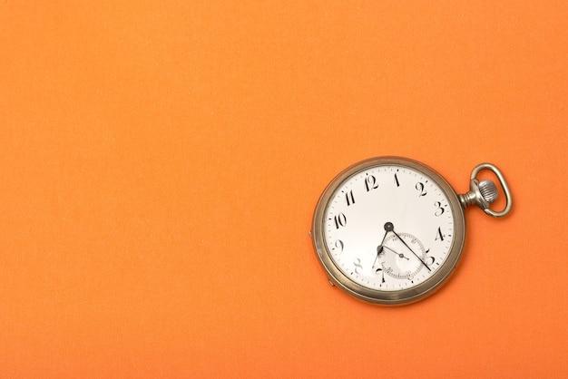 Uhr auf einer orangefarbenen oberfläche - zeitmanagementkonzept