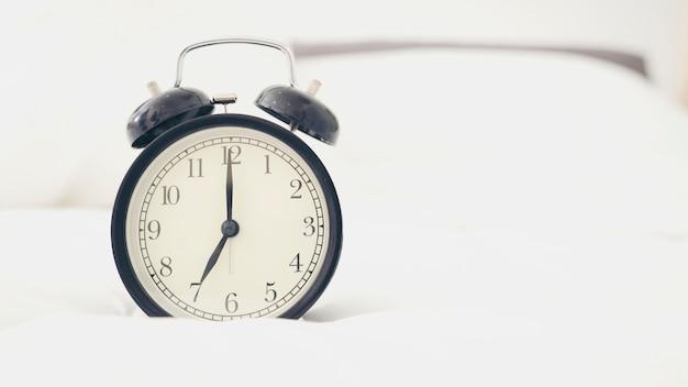 Uhr auf weißem, bequemem bett.