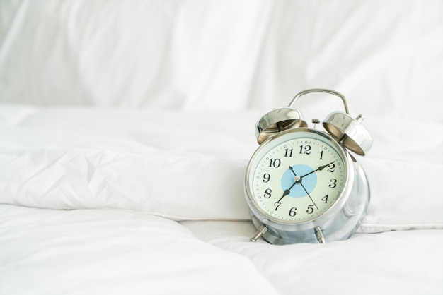 Uhr auf weißem bett