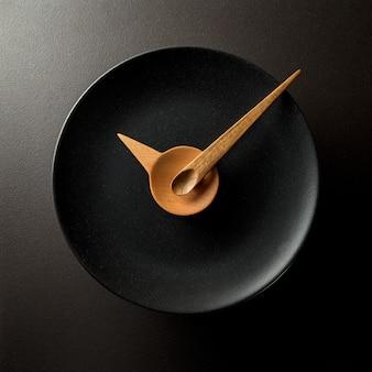 Uhr aus holzlöffeln auf einem schwarzen teller. essenszeitkonzept