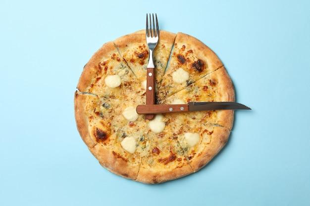 Uhr aus pizza und besteck auf blau