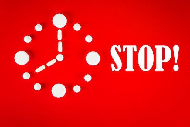 Uhr aus weißen tabletten mit der aufschrift stop, auf rotem hintergrund, ansicht von oben. 2019 neuartiges coronavirus 2019-ncov-konzept.