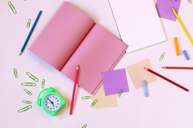 Uhr, briefpapier, leere notizblöcke auf dem tisch, draufsicht