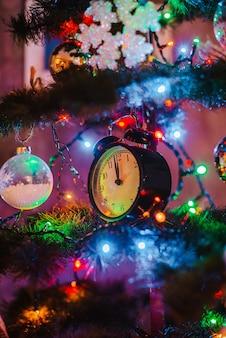 Uhr hängt an einem geschmückten weihnachtsbaum mit girlandenlichtern. mitternacht neujahr.