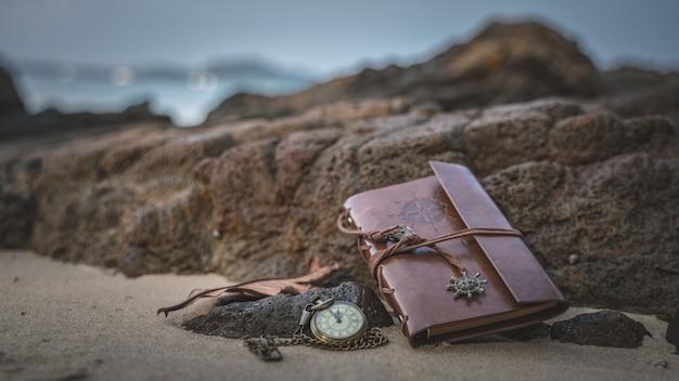 Uhr-halskette und braune ledertasche auf seestein