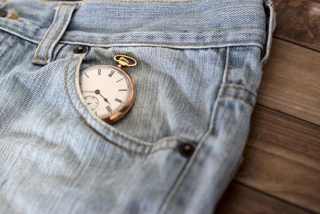 Uhr in einer jeanstasche auf einer holzoberfläche - zeitmanagementkonzept