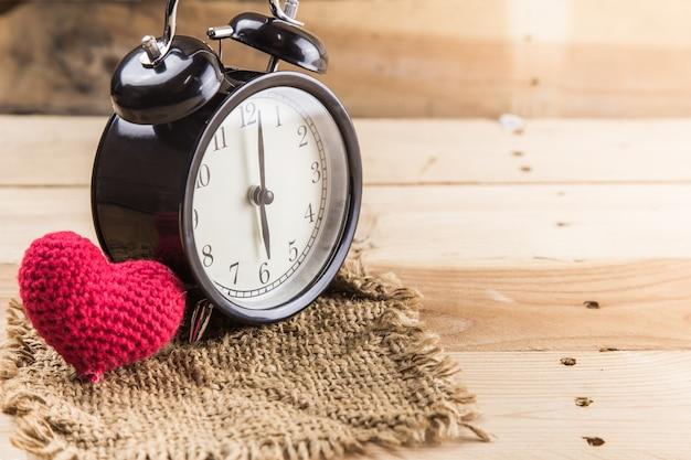 Uhr mit liebesherzen auf hölzernem hintergrundliebeszeitkonzept