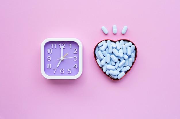 Uhr mit medizinischen blauen pillen auf rosa.