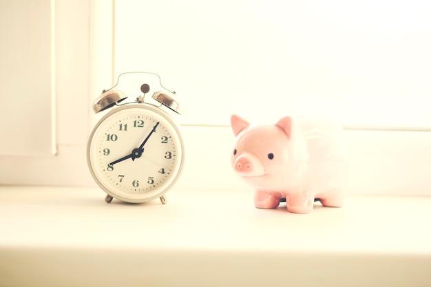 Uhr mit sparschwein am fenster