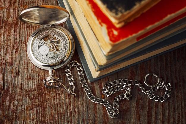 Uhr und ein altes buch auf einem hölzernen hintergrund.