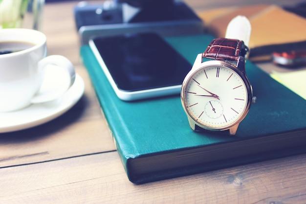 Uhr und telefon auf buch, tasse kaffee auf holztisch?