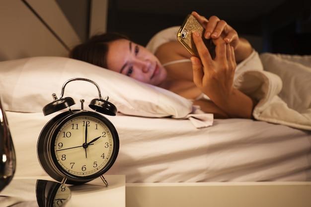 Uhr zeigen 2 uhr und frau mit ihrem smartphone auf dem bett im schlafzimmer