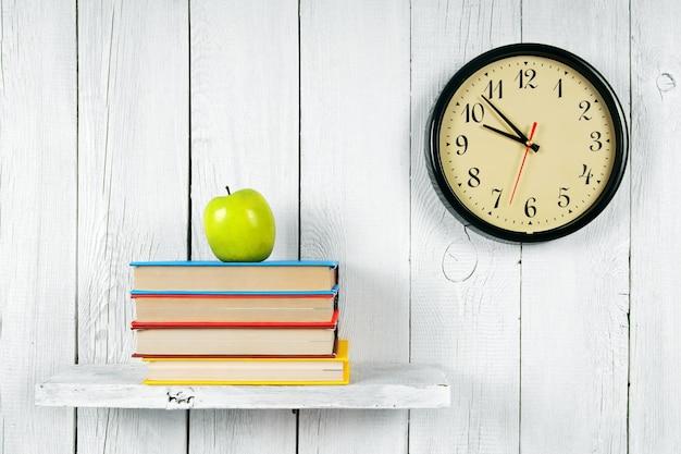 Uhren, bücher und ein grüner apfel auf einem holzregal. auf einem weißen hölzernen hintergrund.