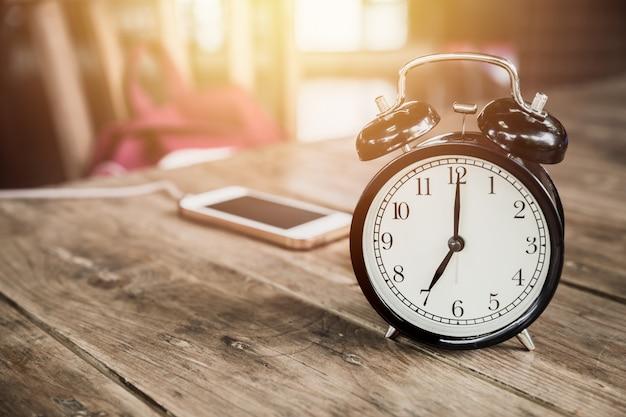 Uhrzeiten um 7 uhr morgen auf hölzerner tabelle mit dem intelligenten telefon, das am caféunschärfehintergrund auflädt.
