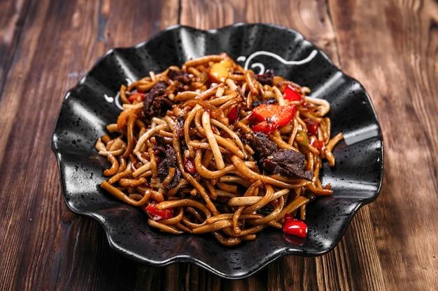 Uigurisches küchengericht tsomyan gebratenes nudelrindfleisch