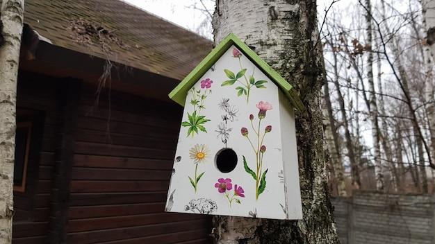 Ukraine, kiew - 17. april 2020. schönes weiß gestrichenes vogelhaus aus holz auf einer birke im wald in der nähe eines braunen landhauses aus holz. hausgemachtes vogelfutter. kunstvogelhaus auf einem baum im garten.