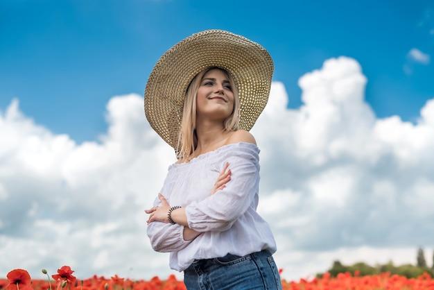 Ukrainische dame, die entlang eines mohnfeldes geht, das konzept der sinnlichkeit, des lebensstils. entspannen