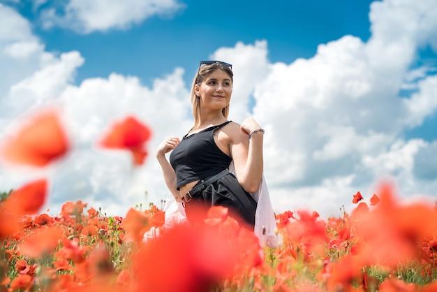 Ukrainische dame, die entlang eines mohnfeldes geht, das konzept der sinnlichkeit, des lebensstils
