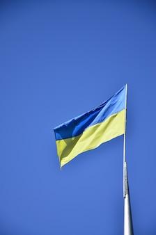 Ukrainische flagge gegen den blauen wolkenlosen himmel. die offizielle flagge des ukrainischen staates umfasst gelbe und blaue farben