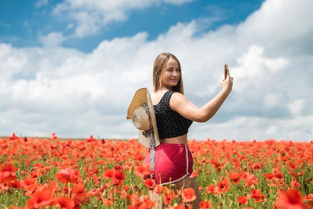 Ukrainische frau in sportbekleidung und strohhut, die ein foto selfie mit smartphone im mohnfeld am sommertag macht.