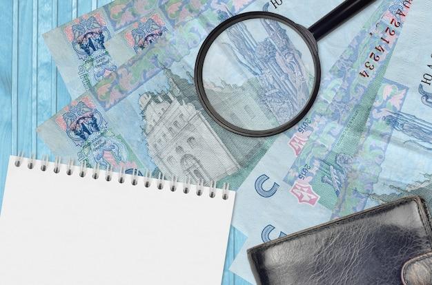 Ukrainische griwna rechnungen und lupe mit schwarzer geldbörse