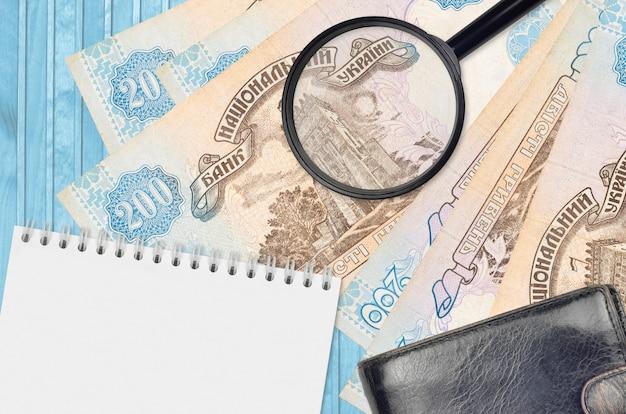 Ukrainische griwna-scheine und lupe mit schwarzer geldbörse und notizblock