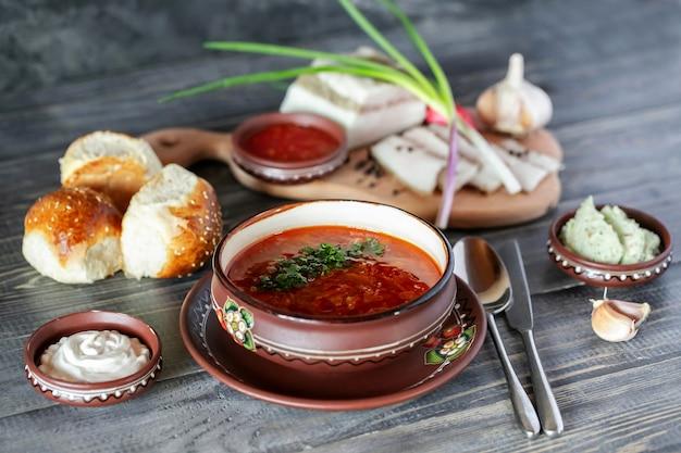Ukrainische suppe bortchsh. traditionelle ukrainische küche. salo wiegt knoblauchzwiebeln und brötchen. saure sahne und saucen.