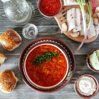 Ukrainische suppe bortchsh. traditionelle ukrainische portion. salo wiegt knoblauchzwiebeln und brötchen. saure sahne und saucen.