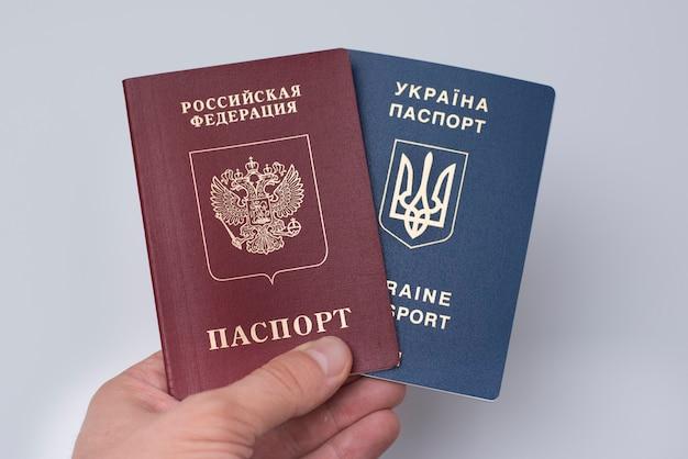 Ukrainische und russische internationale pässe in der hand des mannes. . nahaufnahme