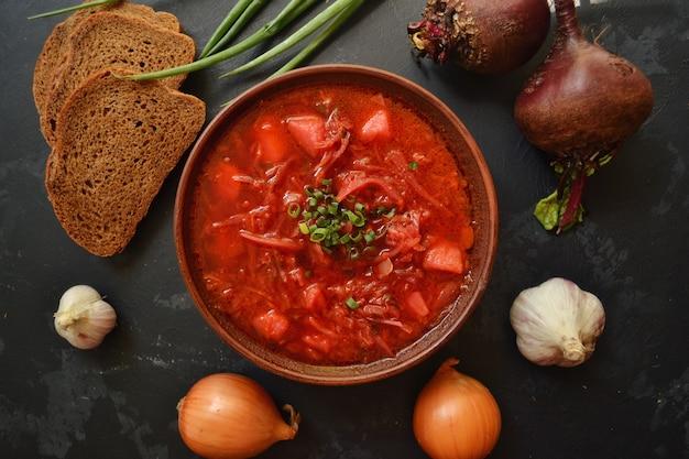 Ukrainische und russische küche. roter borschtsch auf schwarzer oberfläche. borschtsch mit gemüse und tomaten. rüben, zwiebeln, brot, tomaten, kohl, knoblauch.