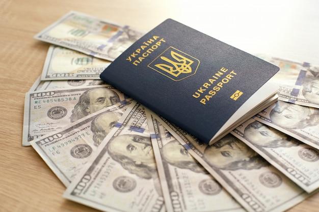 Ukrainischer biometrischer pass und dollar. geld und dokumente für auslandsreisen. dokumente für die einwanderung.