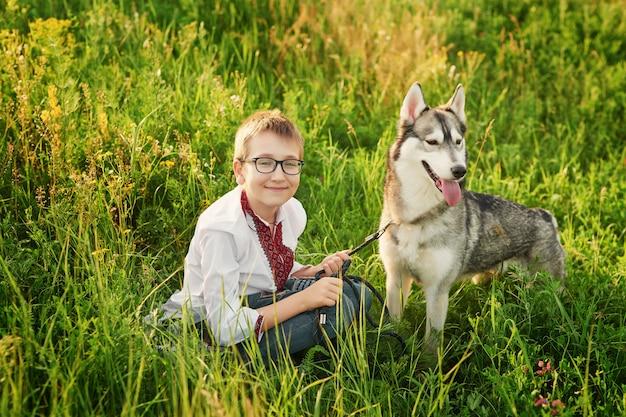 Ukrainischer kinderjunge mit hundeschlittenhund auf einem gebiet im sommer bei sonnenuntergang