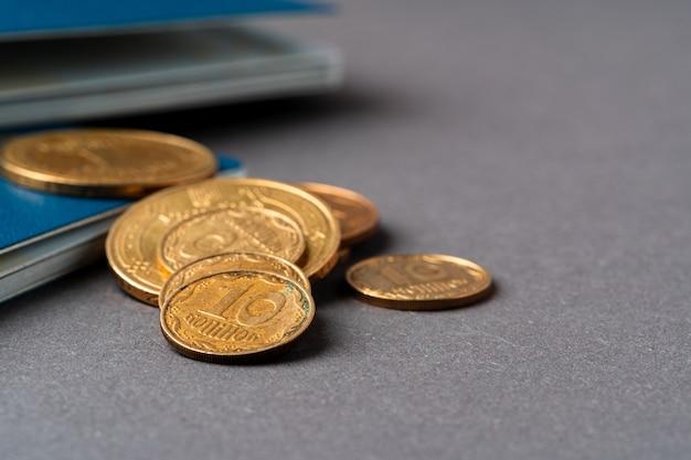 Ukrainischer pass mit ukrainischen griwna-münzen. armuts- und einwanderungskonzept