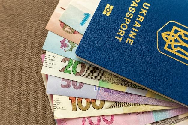 Ukrainischer pass und geld, ukrainische griwna-banknotenrechnungen auf kopierraumhintergrund, draufsicht. konzept für reise- und finanzprobleme.