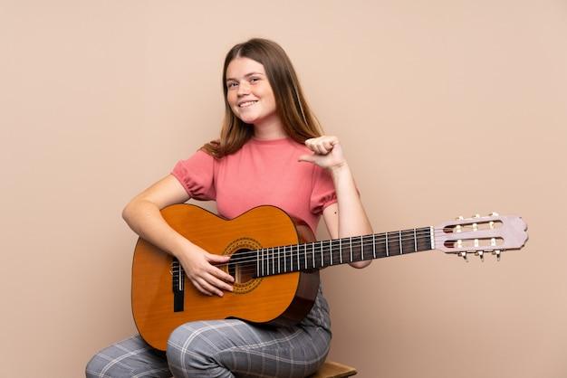Ukrainisches jugendlichmädchen mit gitarre über getrenntem stolzem und selbstzufriedenem