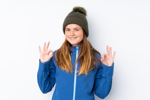 Ukrainisches jugendlichmädchen mit winterhut über dem lokalisierten weiß, das ein okayzeichen mit den fingern zeigt